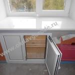 Пластиковый холодильник под окном кирпичного дома